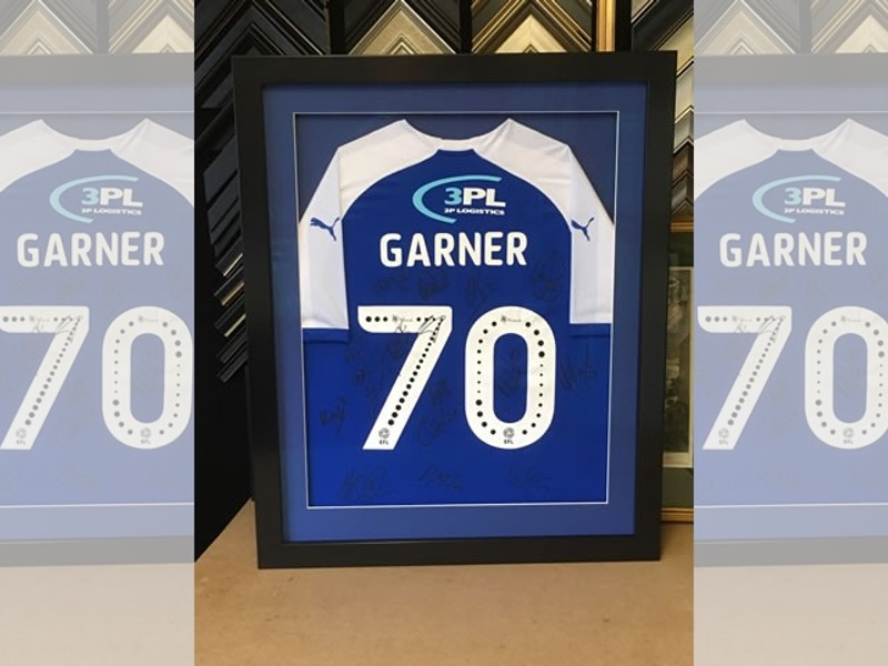 A Wigan Athletic shirt signed by the whole team, framed in a black gloss box frame and glazed with Tru Vue reflection control glass.